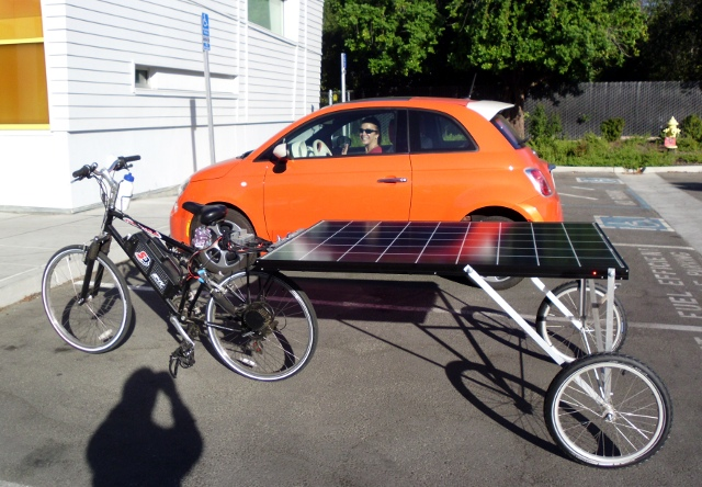 Including the panel, the solar bike is actually longer than the electric car (Fiat 500e) parked next to it.